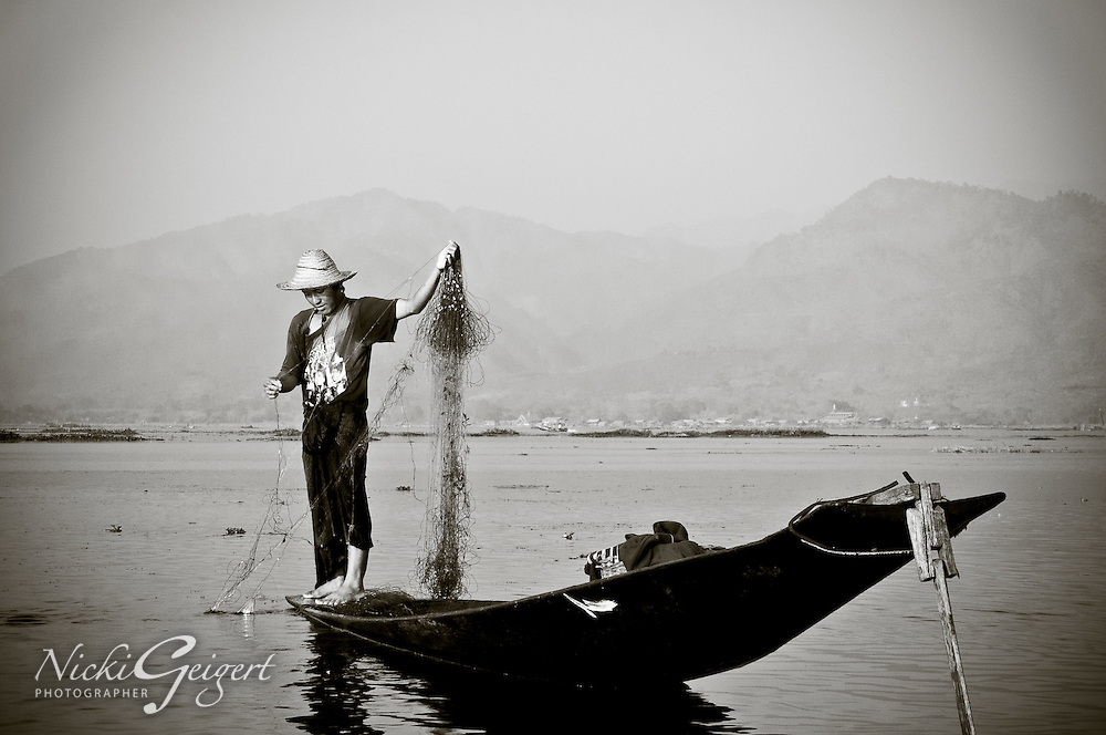 Fisherman on standing canoe gathering his net, Myanmar, black and white. Fine art photography prints. Exotic people and places wall art for sale, stock images