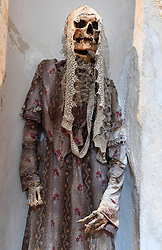 "NO WEB FOR FRANCE - In the crypt of the Capuchin Church of Burgio, a magnificent village situated 100 kilometres south of Palermo,Sicily, Italy on January 2019 the dead are perfectly staged. In all, there are around 50 mummies, most in the upright position, all elegantly dressed. The women wear splendid lace dresses, a little faded, and the men their best hat. Almost all of these mummies date to the 18th and 19th centuries. The most recent were added at the beginning of the 20th century. In the shadows, illuminated with a small bright torch, Luisa Maria Lo Gerfo examines the skull of an elegant bourgeois deceased 150 years ago. Anthropologist, biologist, archaeologist and Sicilian mummy specialist, she regularly works on mummies whether they are in an upright position or elongated in richly decorated open coffins. She measures limbs, diagnoses diseases according to abnormalities and scars, inspects dresses, mantillas, costumes, top hats and scarves. ""Not everyone could afford to be mummified"", she explains. ""The more one was part of high society, the closer one was to the altar, the heart of the church. The poorest were buried outside the church."" Sicily will reveal over time a real research laboratory on mummification. It is spreading throughout the island and there is not an important village in sight that does not display the bodies of their priests, monks or citizens in the crypt of their church. Photo by Eric Vandeville/ABACAPRESS.COM"