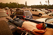 Jeffrey O'Bosky takes a nap at his truck at Shasta College on Friday, July 27, 2018, in Shasta County, Calif. O'Bosky said he lives near Whiskeytown and is staying at the evacuation center at the college campus until further notice from fire officials. His home is threatened by the Carr Fire.