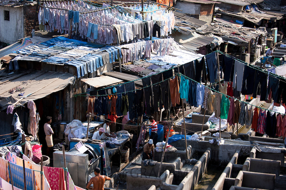 Indian hand laundry, Dhobi Ghat, and laundrymen using traditional flogging stones to wash clothing at Mahalaxmi, Mumbai, India