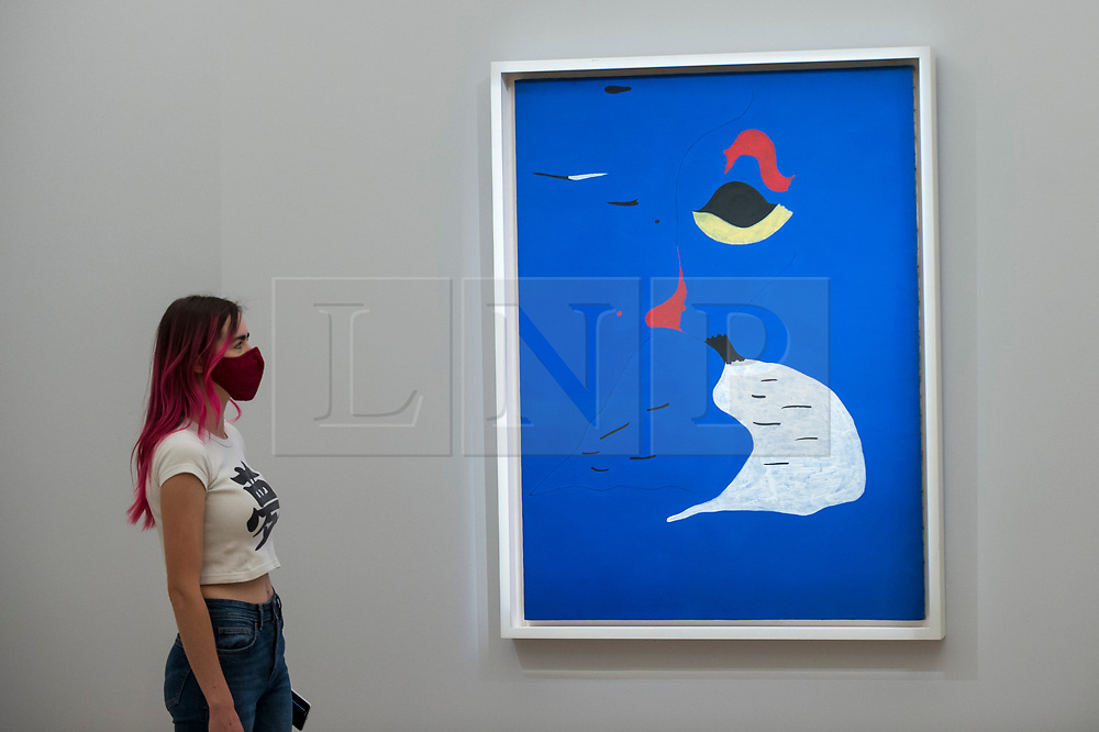 """© Licensed to London News Pictures. 23/07/2020. LONDON, UK.  A visitor views """"Peinture (Femme au chapeau rouge) (1927) by Joan Miró, estimate: £20-30 million. Preview of works on display at Sotheby's London ahead of a one-off auction on July 28.  Titled 'Rembrandt to Richter', the sale will offer the very best from Old Masters, Impressionist & Modern Art, Modern & Post-War British Art and Contemporary Art.  The exhibition is open to the public at Sotheby's New Bond Street galleries until July 28. [Image embargoed for release until 9am BST 24 July 2020].  Photo credit: Stephen Chung/LNP"""