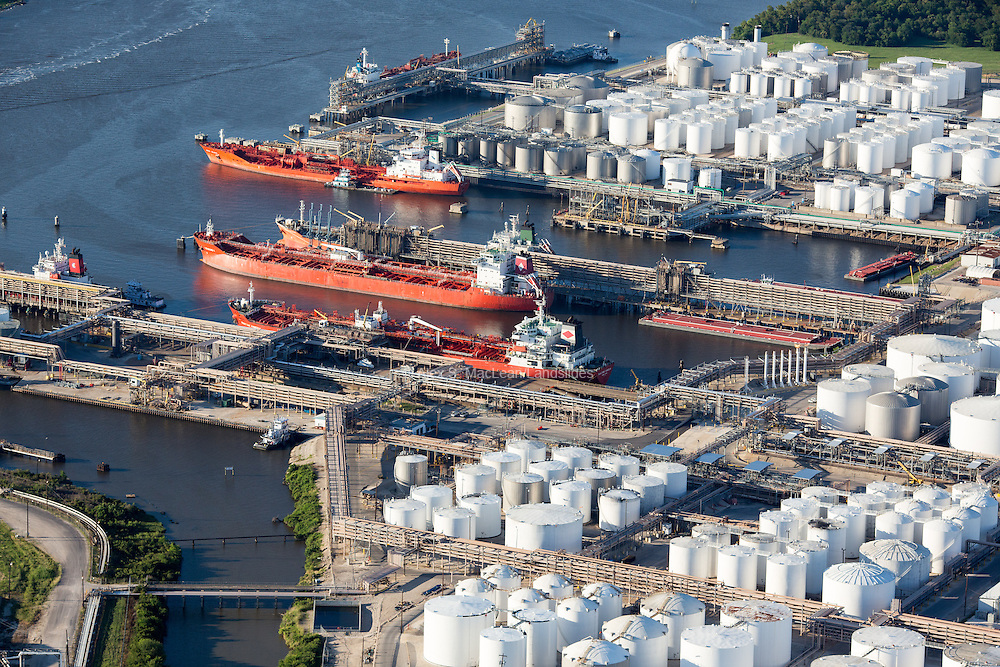 Barges sit by storage tanks along the Houston Ship Channel