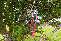 A dream catcher is blown by the breeze. With a fourth person charged for the murder of 17 year-old Jodie Chesney, purple themed tributes, including a garden,  can be seen at St Neot's Open space. Romford, London, May 27 2019.