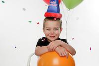 Tucker Ward 5 year old birthday boy photo in studio celebrating with balloons.