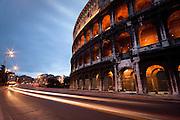 The Roman Coliseum with headlights on Via dei Fori Imperiali, Rome, Lazio, Italy.