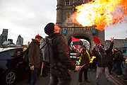 Anarchists gather as a black bloc for the Fuck Parade to party and protest at the class and wealth divide between rich and poor and the gentrification of London, the demonstration was organised by anarchist group Class War on May 1st 2016 in London, United Kingdom. The parade is now part of the May Day activism calendar as dissatisfaction about the establishment, the police and the inadequacy of the press is highlighted. A fire breather shoots up a flame at the protest gathers on Tower Bridge.
