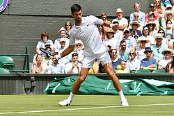 © Licensed to London News Pictures. 01/07/2019. London, UK. Novak Djokovic of Serbia drinks a bottle of Evian water whilst playing Philipp Kohlschreiber of Germany in the first round mens singles mens singles 1st round draw of the Wimbledon Tennis Championships 201 on Day 1 held at the All England Lawn Tennis and Croquet Club. Photo credit: Ray Tang/LNP