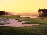 Fog covers the back of a golf course at sunrise