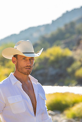 hot cowboy in sunset light by a river