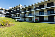 Exterior modern white condominium building with lots of lawn, nobody inside