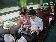 06 APRIL 2012 - HAI PHONG, VIETNAM: A couple surfs the internet on a laptop using a broadband card in the 3rd class car on the Hanoi to Hai Phong Express. The train has three classes: 1st, 2nd and 3rd. Tickets cost between $3(US) and $2(US) one way. The Hanoi to Hai Phong Express Train runs several times a day between Long Bien Station in Hanoi and the Hai Phong Station. Hanoi is the capital of Vietnam and Hai Phong is the 4th largest city in Vietnam. Hai Phong is the principal industrial port in the northern part of Vietnam. It was heavily bombed and mined during the American War (what Americans call the Vietnam War).   PHOTO BY JACK KURTZ