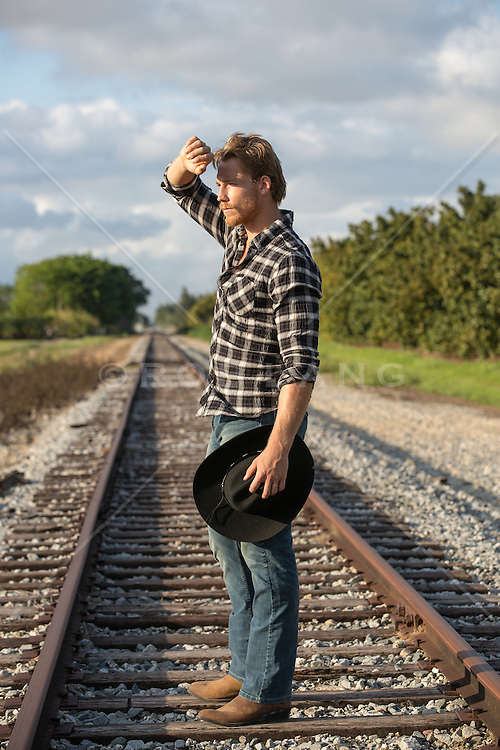 cowboy standing on a railroad track with his hand up to block the harsh sun