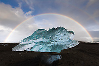 A rainbow appears over a beached iceburg, southern Iceland
