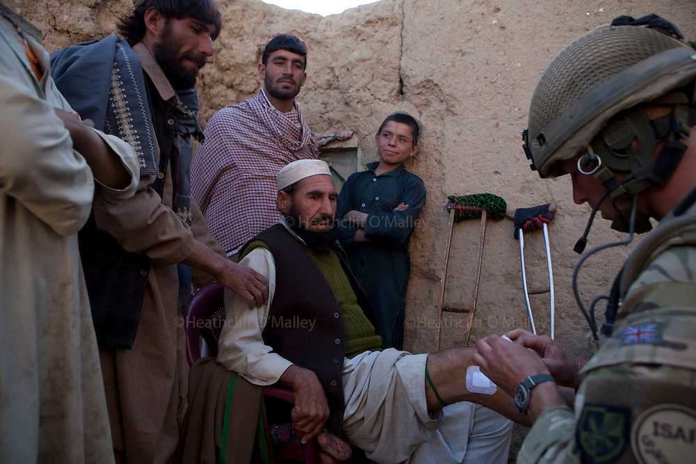Mcc0027461 . Daily Telegraph..Mullah Abdullahjan shows the wound he received recently possibly inflicted by ISAF forces on a previous operation having his healing wound cleaned and redressed by medic LCpl Glen McAllister..Paratroopers from A coy, 3 Para under the command of Lt Jamie Macdonald on patrol south of their base CP Qudtrat in the northern Nad e Ali district of Helmand. ..Helmand 2 December 2010