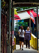 02 AUGUST 2018 - PAK KRET, NONTHABURI, THAILAND: People cross a bridge over a small stream on Ko Kret. Ko Kret (also spelled Koh Kret) is a small island in the Chao Phraya River in Nonthaburi province north of Bangkok. It is about 2 km long and 1 km wide. It has seven main villages, the largest and most populous being Ban Mon. Ko Kret was created in 1722 when a canal was dug in the Chao Phraya River to bypass a bend. Most of the people on the island are ethnically Mon, from the hills of western Thailand and eastern Myanmar (Burma). The island is popular as a weekend daytrip from Bangkok. The island is famous for the Mon style pottery made on the island.      PHOTO BY JACK KURTZ