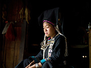 Portrait of a young Akha Nuquie woman wearing her traditional clothing at home in Ban Chakhampa, Phongsaly province, Lao PDR. Her traditional costume is made from hand woven cotton and dyed with indigo and decoarated with hand embroidery typical of the Akha Nuquie sub-group; the high headdress distinguishes her as a married women. One of the most ethnically diverse countries in Southeast Asia, Laos has 49 officially recognised ethnic groups although there are many more self-identified and sub groups. These groups are distinguished by their own customs, beliefs and rituals.