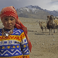 A nomadic Kyrgyz girl stands near her family's camels and summer hut in the Pamir Mountains of Xinjiang Province in far western China.