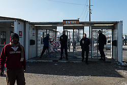 October 23, 2016 - Calais, France - Police officers secure in the Calais Jungle the entrance of the official part of the camp in Calais, France, on 23 October 2016. The refugee camp on the coast to the English Channel is to be cleared on monday, according to the French government. The approximately 8,000 refugees are distributed to various reception centers in France. (Credit Image: © Markus Heine/NurPhoto via ZUMA Press)