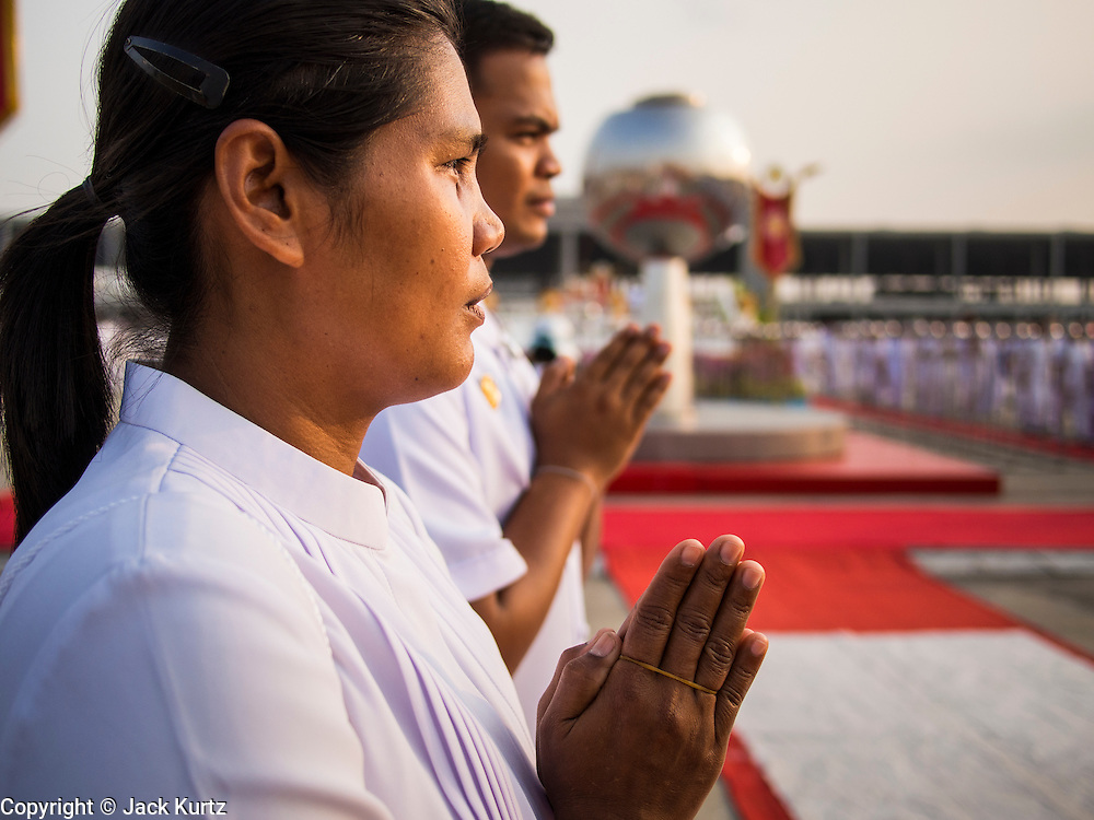 """14 FEBRUARY 2014 - KHLONG LUANG, PATHUM THANI, THAILAND: A woman prays during the opening of evening Makha Bucha Day services at Wat Phra Dhammakaya. The aims of Makha Bucha Day are: not to commit any kind of sins, do only good and purify one's mind. It is a public holiday in Cambodia, Laos, Myanmar and Thailand. Many people go to the temple to perform merit-making activities on Makha Bucha Day. The day marks four important events in Buddhism, which happened nine months after the Enlightenment of the Buddha in northern India; 1,250 disciples came to see the Buddha that evening without being summoned, all of them were Arhantas, Enlightened Ones, and all were ordained by the Buddha himself. The Buddha gave those Arhantas the principles of Buddhism, called """"The ovadhapatimokha"""". Those principles are:  1) To cease from all evil, 2) To do what is good, 3) To cleanse one's mind. The Buddha delivered an important sermon on that day which laid down the principles of the Buddhist teachings. In Thailand, this teaching has been dubbed the """"Heart of Buddhism."""" Wat Phra Dhammakaya is the center of the Dhammakaya Movement, a Buddhist sect founded in the 1970s and led by Phra Dhammachayo.    PHOTO BY JACK KURTZ"""