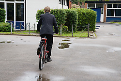 Secondary school student cycling in playground,