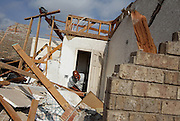 Raymond Butler tries to open a door as he shows contractors damage in his home, a result of the tornado that touched down the night before in Rice, Texas, October 25, 2010.