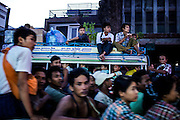 Shared taxis race past eachother during rush hour on the congested streets of Mandalay. The lack of street lights makes for a chaotic scene every evening.