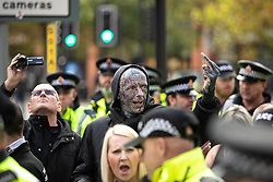 """© Licensed to London News Pictures . 20/10/2018 . Manchester , UK . A man wearing a hoodie with """" 88 """" and with numerous far-right tattoos at the EDL demonstration . 88 is used by far-right groups to stand for HH or Heil Hitler . Hundreds of police contain approximately 50 EDL supporters in Piccadilly Gardens . Street protest movement , the English Defence League ( EDL ) , hold a demonstration , opposed by anti-fascists , including Unite Against Fascism ( UAF ) , in Manchester City Centre . Amongst the reasons for their protest , the EDL cite news reports that revealed an imam at the Didsbury Mosque where Manchester Arena bomber Salman Abedi prayed , praised armed jihad in a sermon delivered just days before Abedi bought a ticket for the Ariana Grande concert at which he killed twenty two people . Photo credit : Joel Goodman/LNP"""