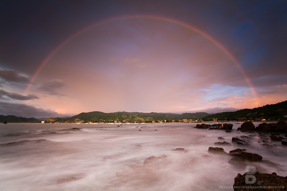 Paradise found as a rainbow fills the sky during sunset, and ocean waters flow around rocks in the coastal fishing port of Puerto Lopez, Ecuador.