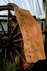 leather chaps hanging on an old wagon wheel