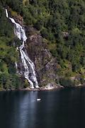 Little boat at the foot of a waterfall in Geirangerfjord | Liten båt ved foten av en foss i Geirangerfjord.