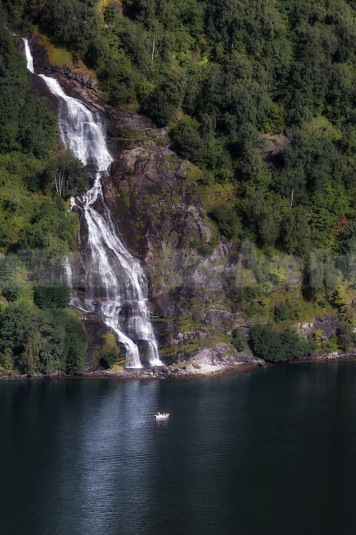 Little boat at the foot of a waterfall in Geirangerfjord   Liten båt ved foten av en foss i Geirangerfjord.