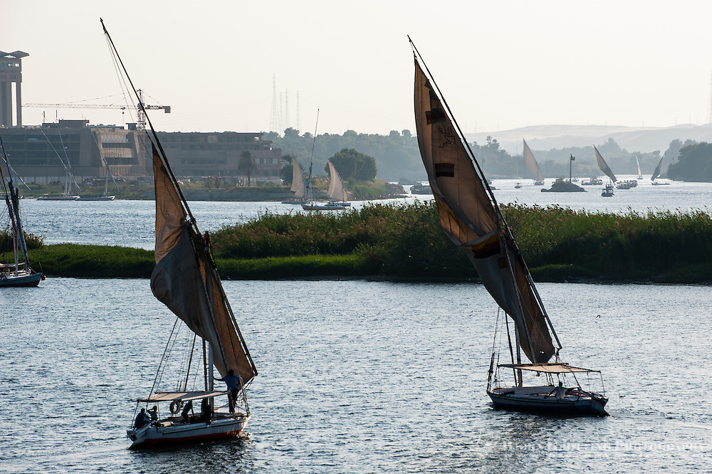 Egypt. Aswan stands on the east bank of the Nile. A felucca is a traditional wooden sailing boat.