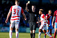 Doncaster Rovers defender Paul Downing (31), on loan from Blackburn Rovers, is shown a yellow card from referee John Brooks during the EFL Sky Bet League 1 match between Scunthorpe United and Doncaster Rovers at Glanford Park, Scunthorpe, England on 23 February 2019.