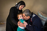 Jamila Alrazouk (L) hands grandson Riad Alsaloum, 1, to his grandfather and her husband, also named Riad Alsaloum, who plants a kiss on the toddler's cheek at the family apartment in Tampa, Florida, U.S. After being released from the hospital for the first time, Riad Alsaloum was overjoyed to see his grandson upon arriving at the family's temporary apartment.