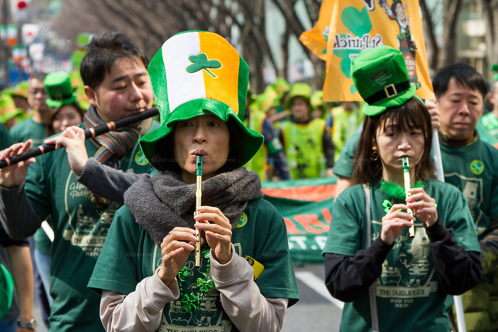 """Japanese people play traditional Irish music at the 27th Saint .Patrick's Day Parade in Omotesando, Tokyo, Japan. Sunday March 17th 2019. Started in 1992 by the Irish Network, Japan, and supported by the Embassy of Ireland,; the parade, along with the """"I Love Ireland Festival"""" held nearby is Asia's  largest Irish event."""