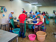 "11 JUNE 2015 - MAHACHAI, SAMUT SAKHON, THAILAND: Burmese migrant workers at the Samut Sakhon shrimp market clean and process farm raised shrimp. Labor activists say there are about 200,000 migrant workers from Myanmar (Burma) employed in the fishing and seafood industry in Mahachai, a fishing port about an hour southwest of Bangkok. Since 2014, Thailand has been a Tier 3 country on the US Department of State Trafficking in Persons Report (TIPS). Tier 3 is the worst ranking, being a Tier 3 country on the list can lead to sanctions. Tier 3 countries are ""Countries whose governments do not fully comply with the minimum standards and are not making significant efforts to do so."" After being placed on the Tier 3 list, the Thai government cracked down on human trafficking and has taken steps to improve its ranking on the list. The 2015 TIPS report should be released in about two weeks. Thailand is hoping that its efforts will get it removed from Tier 3 status and promoted to Tier 2 status.        PHOTO BY JACK KURTZ"