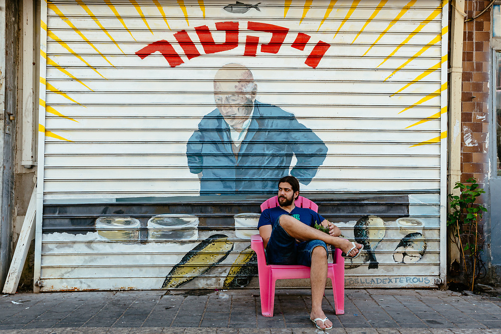 Zaky German, a local Israeli resident of Tel Aviv, is seen enjoying fresh juice as he relaxes on a chair in front of a closed store, during a hot summer afternoon at Levinsky Street, a pedestrian zone in the Levinsky Market area in southern Tel Aviv, Israel, on August 19, 2020. A ban on vehicles in Levinsky Street was started at the end of 2019, as a pilot of a new municipality initiative to reduce the number of private cars in the inner city.<br /> The Tel Aviv-Jaffa  Municipality is planning to convert 11 popular streets in the city, into pedestrian zones shut to vehicles in the coming months.