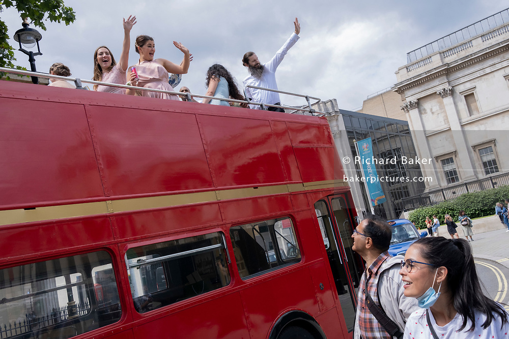 A joyous wedding party drives through Trafalgar Square, on the open top deck of a hired London Routemaster bus, on 8th July 2021, in London, England.