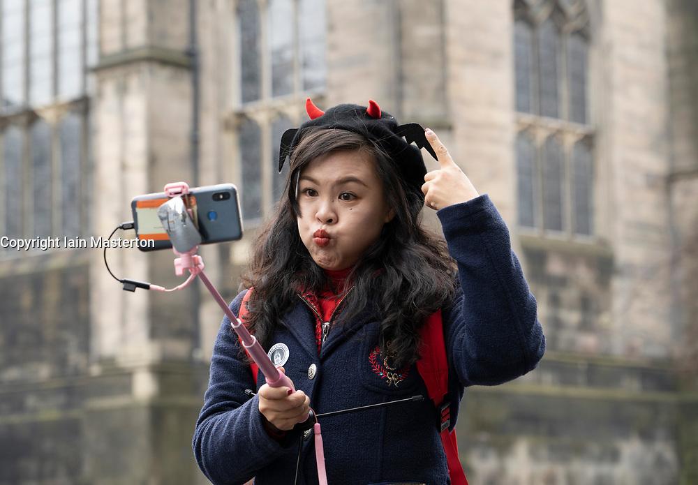 Edinburgh, UK. 8 Feb 2019. Young Chinese female tourist making funny face while taking selfie photo in Old Town of Edinburgh, Scotland, UK