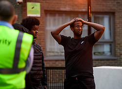 © Licensed to London News Pictures. 23/06/2017. London, UK. A man holds his head in his hands as residents are evacuated from the Taplow block of the Chalcots Estate in Camden after it failed a fire inspection because of combustable cladding. Prime Minister Theresa May has told Parliament that up to 600 high rise tower blocks may have similar cladding to that found in Grenfell Tower, which went on fire last week, in which as many as 79 residents are thought to have perished Photo credit: Ben Cawthra/LNP