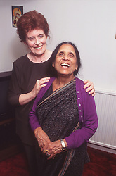 Elderly woman standing with carer laughing,