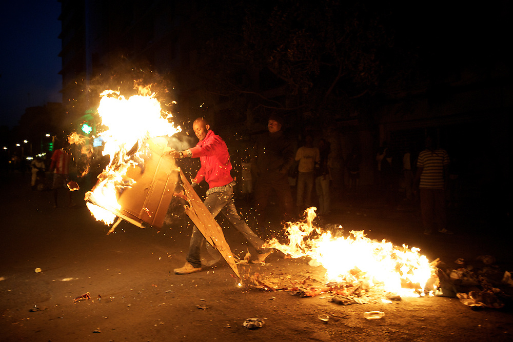 February 23, 2012 - Dakar, Senegal: A opposition supporter sets alight a road block during a protest against the candidature of the current president Abdoulaye Wade for a anti-constitutional third candidature to as head of state. Tensions between police and opposition supporters have been high in the capital Dakar and other cities around the country, where some clashes have happen ahead of the presidential elections on the 26th of February. At least fourteen people have died in the past month. (Paulo Nunes dos Santos/Polaris)