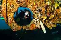 A diver looks through a Lesleen M freighter wreck's porthole covered in corals and tube sponges, Castries, St. Lucia.