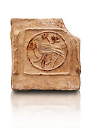 6th-7th Century Eastern Roman Byzantine  Christian Terracotta tiles depicting a bird - Produced in Byzacena -  present day Tunisia. <br /> <br /> These early Christian terracotta tiles were mass produced thanks to moulds. Their quadrangular, square or rectangular shape as well as the standardised sizes in use in the different regions were determined by their architectonic function and were designed to facilitate their assembly according to various combinations to decorate large flat surfaces of walls or ceilings. <br /> <br /> Byzacena stood out for its use of biblical and hagiographic themes and a richer variety of animals, birds and roses. Some deer and lions were obviously inspired from Zeugitana prototypes attesting to the pre-existence of this province's production with respect to that of Byzacena. The rules governing this art are similar to those that applied to late Roman and Christian art with, in the case of Byzacena, an obvious popular connotation. Its distinguishing features are flatness, a predilection for symmetrical compositions, frontal and lateral representations, the absence of tridimensional attitudes and the naivety of some details (large eyes, pointed chins). Mass production enabled this type of decoration to be widely used at little cost and it played a role as ideograms and for teaching catechism through pictures. Painting, now often faded, enhanced motifs in relief or enriched them with additional details to break their repetitive monotony.<br /> <br /> The Bardo National Museum Tunis, Tunisia.  Against a white background.