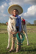 """Francisco """"Panchito"""" Flores, 11, is a young charro learning the Mexican rodeo tradition of charreada. Panchito is a third-generation """"charro,"""" the Spanish word for cowboy, in his hometown of San Antonio, Texas.<br /> <br /> Panchito rides up Guera Chabela, a 26-year-old pony, who was originally trained by his grandfather at the Espuelas de Plata Ranch in Katy, Texas on October 5, 2018. Expertise with a lasso is a key skill for any charro. Several of the events of the charreada call for lassoing a steer or horse and extra points are given for the decorative flourishes of the charro with his rope.<br /> <br /> A charro wears a suit, called a """"traje,"""" for competition that is based on a 19th century outfit consisting of tight and decorated pants, leather chaps, a silk tie, and a wide-brimmed sombrero. These suits must be made of the same materials and technology of the 19th century, so buttons and bone stays are common.<br /> <br /> Panchito began training to be a charro at age three when his father Francisco taught him how to spin a lasso. At age four, Panchito began riding horses. <br /> <br /> He practices for an hour a day on Guera Chabela and his other competition horse. Panchito competes in bull riding, manganas a pie (roping on foot), manganas a caballo (roping on horseback), coleadero (steer tailing), a won a championship in youth charreada two years ago for El Paso de la Muerte (The pass of death)."""
