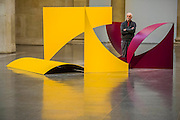 Phillip King with Dunstable Reel 1970, Painted steel. Phillip King exhibition at the Tate Britain, to mark his 80th birthday. The display celebrates King's significant contribution to late 20th century sculpture through six colourful sculptures. These are his key works from the 1960s and include a variety of unusual shapes and forms, demonstrate King's experimentation with abstraction, construction, material and colour. They include iconic sculptures such as Genghis Khan 1963, a conical structure with a pair of antler-like forms and Rosebud 1962, his first coloured sculpture using fibreglass. The works are displayed in the grand surroundings of the Duveen galleries at Tate Britain.