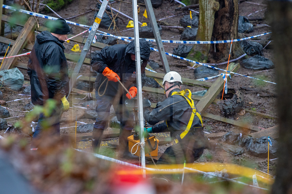 © Licensed to London News Pictures. 17/12/2019. Beaconsfield, UK. A member of a search team wearing a dry suit and a harness is helped by a colleague to retrieve equipment from an ingress point to what appears to be an underground area. London's Metropolitan Police Service have called in the forces specialist Under Water and Confined Space Search Team as they continue to search woodland in Beaconsfield. The Met confirmed on 12th December 2019 they are searching the woodland in Beaconsfield, Buckinghamshire in connection with the disappearance and murder of Mohammed Shah Subhani. Police have been in the area conducting operations on Hedgerley Lane since Thursday 5th December 2019 and are combing wooded area with specialist officers assisted by specialist search dogs. Photo credit: Peter Manning/LNP