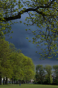 The dark skies of an approaching rain storm approach a park user in Ruskin Park in Lambeth, south London, on 24th May 2021, in London, England.