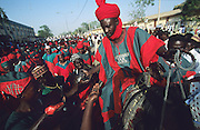 Wages are handed out to members of a Emir's militia dressed in Islamic colors of green and red, during the Durbar Fantasia..The Durbar Fantasia, is the moment where The Husa residents of Kano wear traditional dress, their local leaders and chiefs mount horses, and together with their militias display allegiance and homage to their leader, the Emir of Kano. This takes place after Ramadan. The Emir is Kano's State official political and economic feudal leader, everyone seeks to be in his pleasure, otherwise they reap the consequences..Kano is the largest Muslim Husa city, under the feudal, political and economic rule of the Emir. Kano and the other eleven northern states are under Islamic Sharia Law which is enforced by official state apparatus including military and police, Islamic schools and education, plus various volunteer Militia groups supported financially and politically by the Emir and other business and political bodies. 70% of the population live below the poverty line. Kano, Kano State, Northern Nigeria, Africa