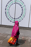 A woman wearing a bright pink raincoat and hood, carries a Sainsbury's bag for life, past a retailer's slogan promoting post-Covid spending on Oxford Street, on 24th May 2021, in London, England.